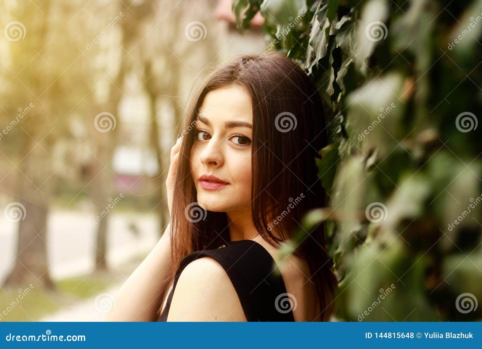 Porträt der durchdachten jungen hübschen Frau an der Straße
