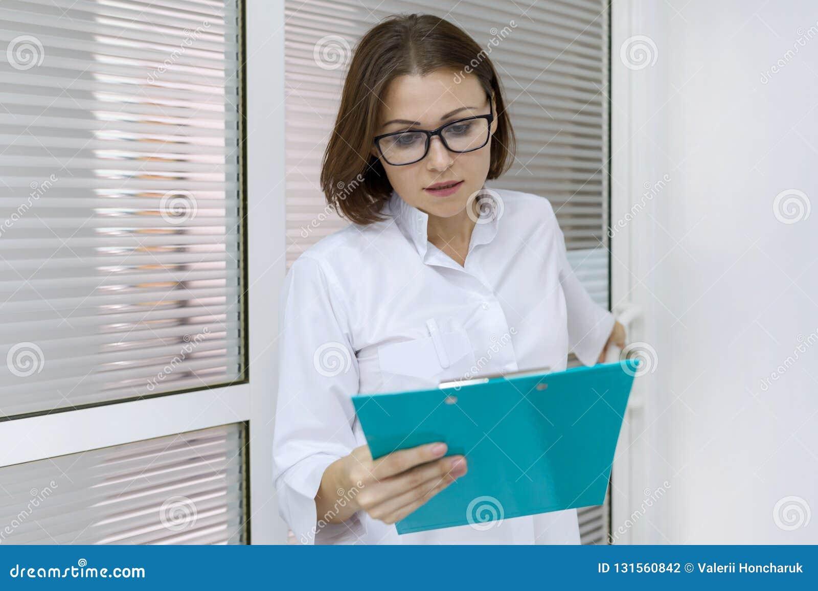 Porträt der erwachsenen weiblichen Krankenschwester, Frau mit dem Klemmbrett, arbeitend im Krankenhaus