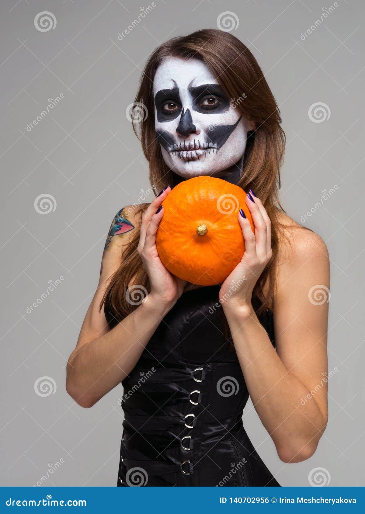 Porträt der Frau mit skeleton Make-up Halloweens, das Kürbis über grauem Hintergrund hält
