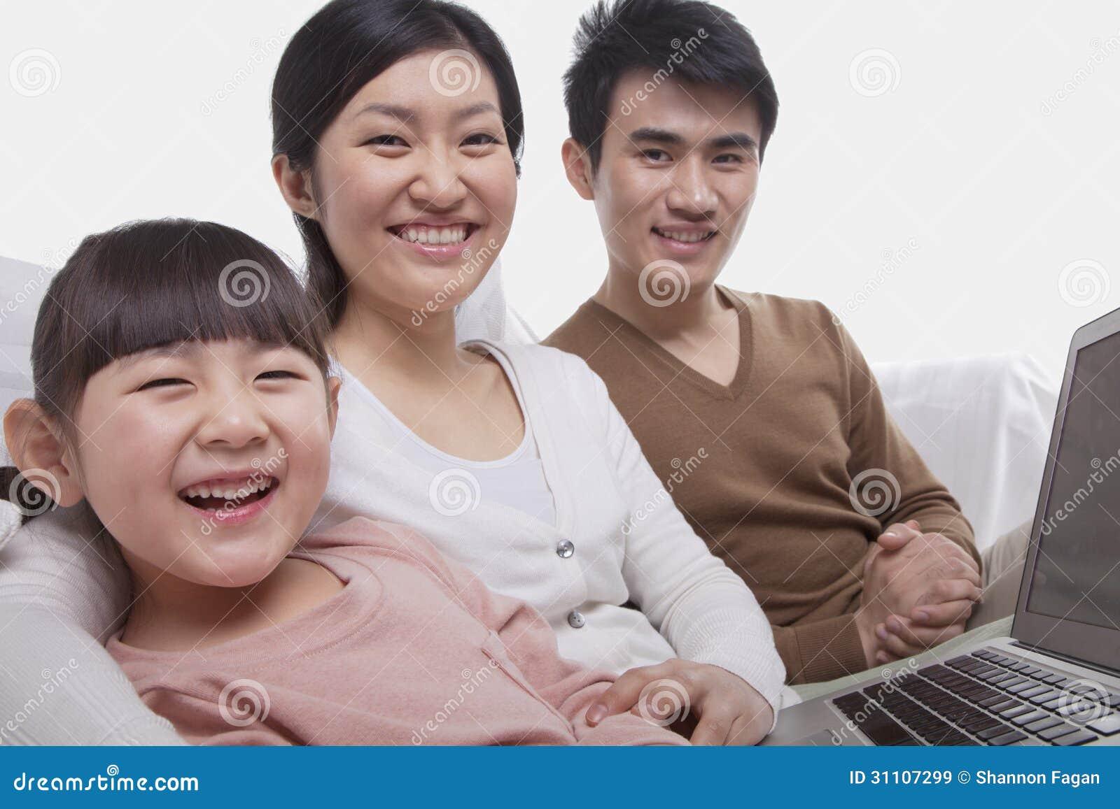 Porträt der glücklichen lächelnden Familie, die auf dem Sofa unter Verwendung des Laptops, Kamera betrachtend, Atelieraufnahme sit