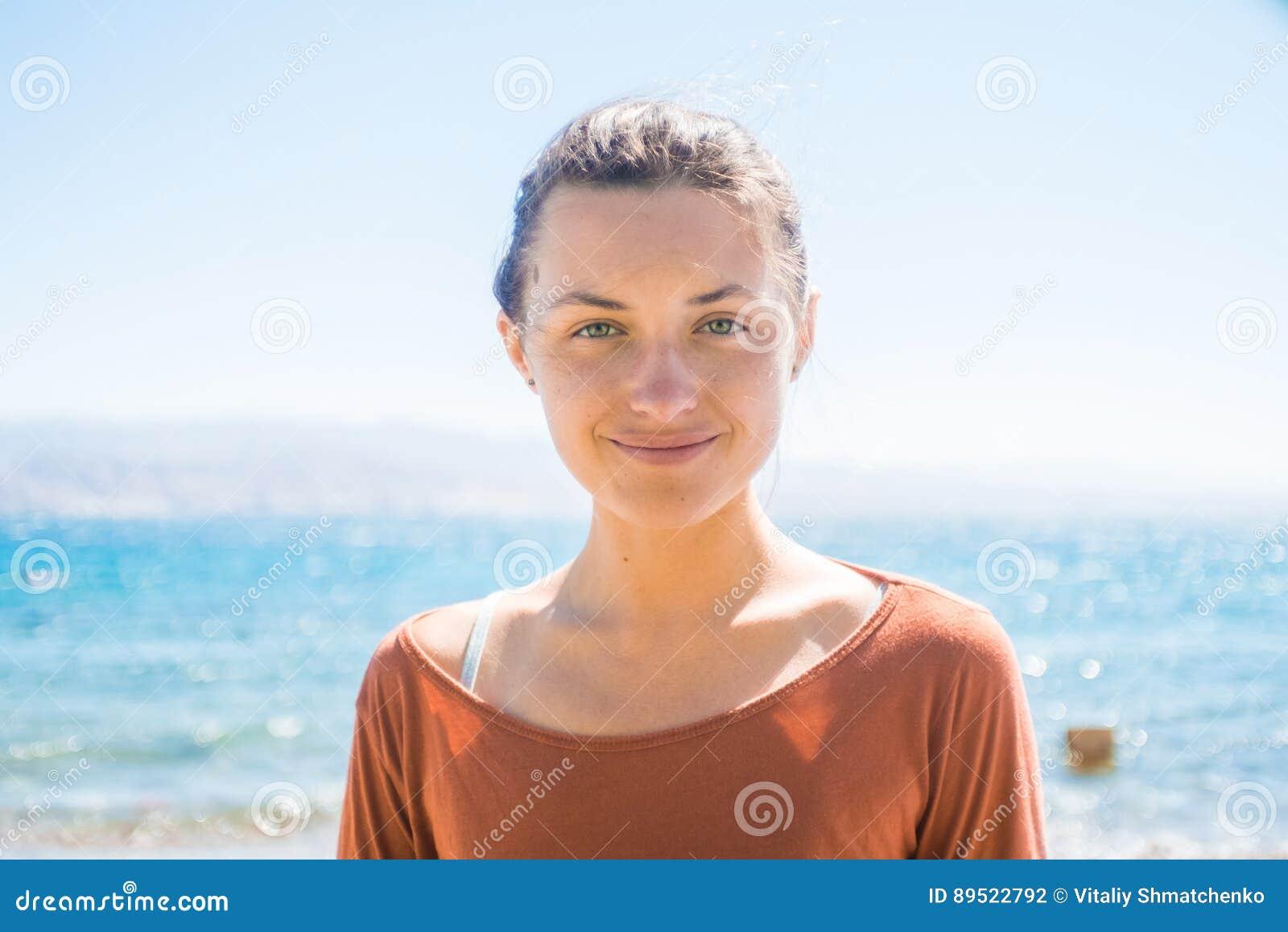 Porträt der glücklichen lächelnden jungen Frau auf dem Strand mit Seehintergrund