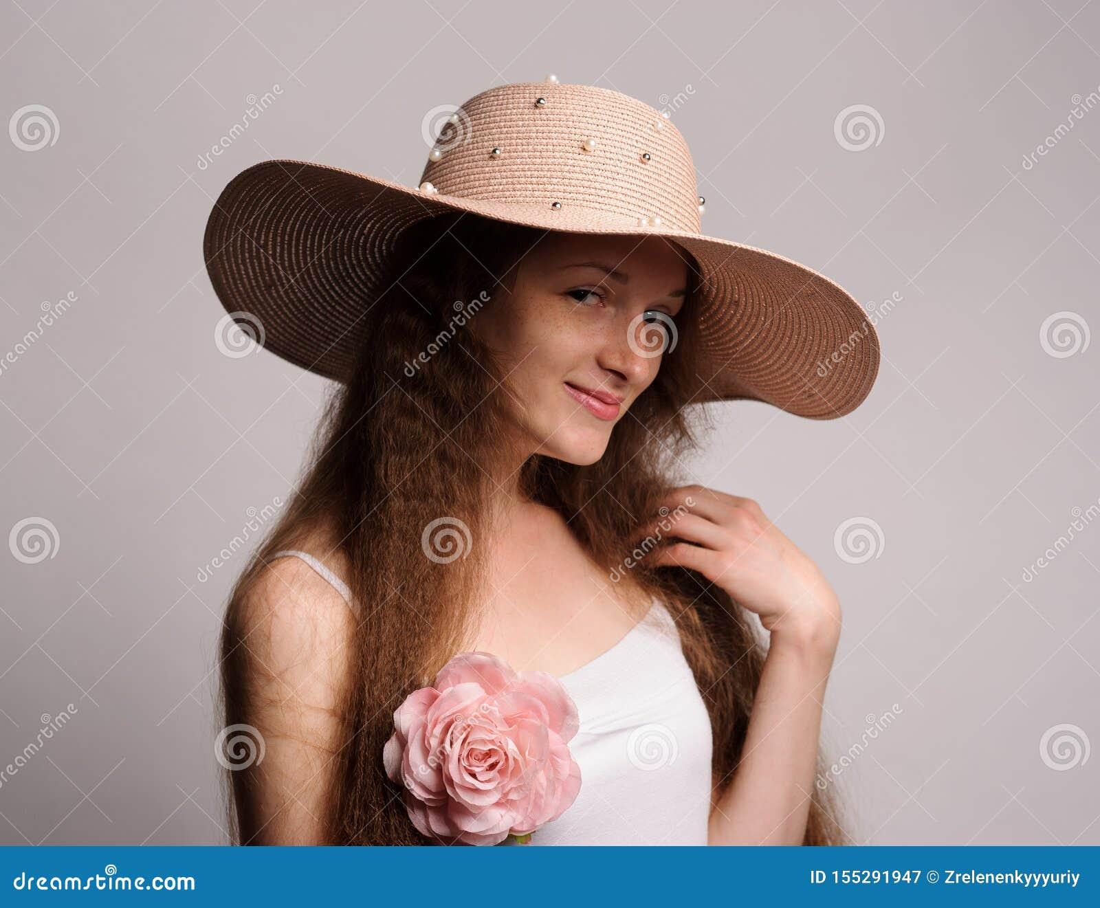 Porträt der hübschen Frau im rosa Hut