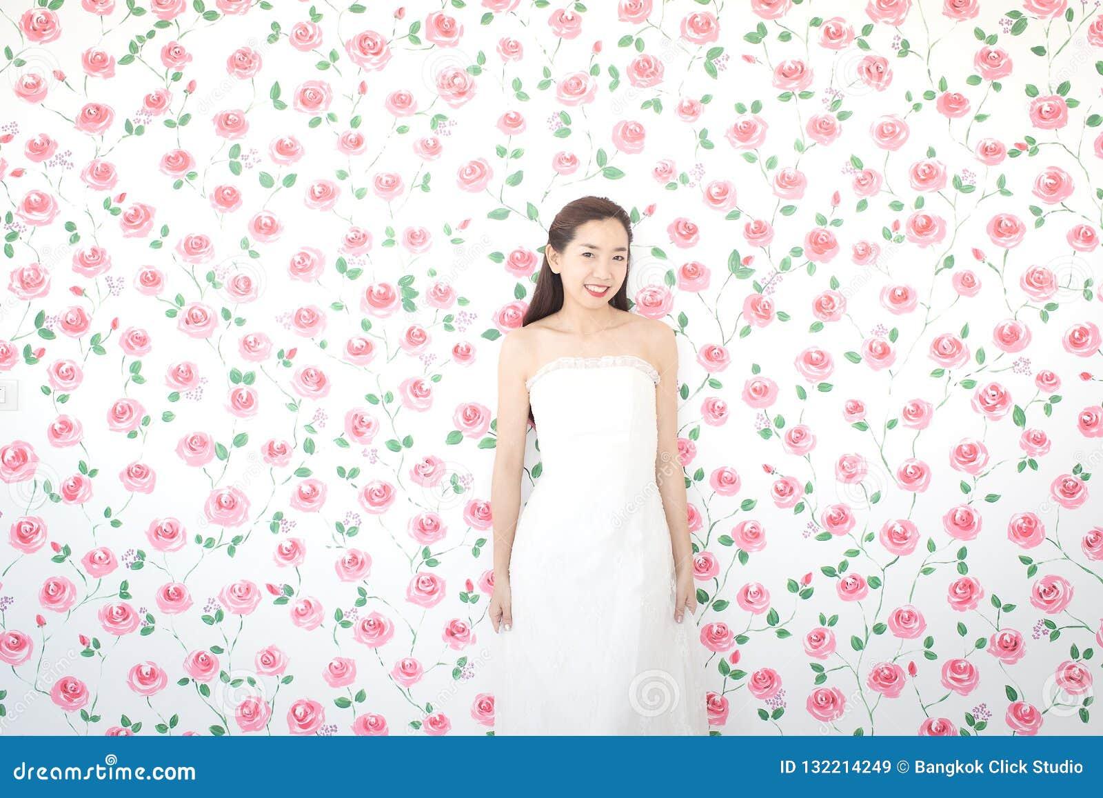 Porträt der jungen asiatischen Braut, die an der Kamera, rosa Rosen lächelt und