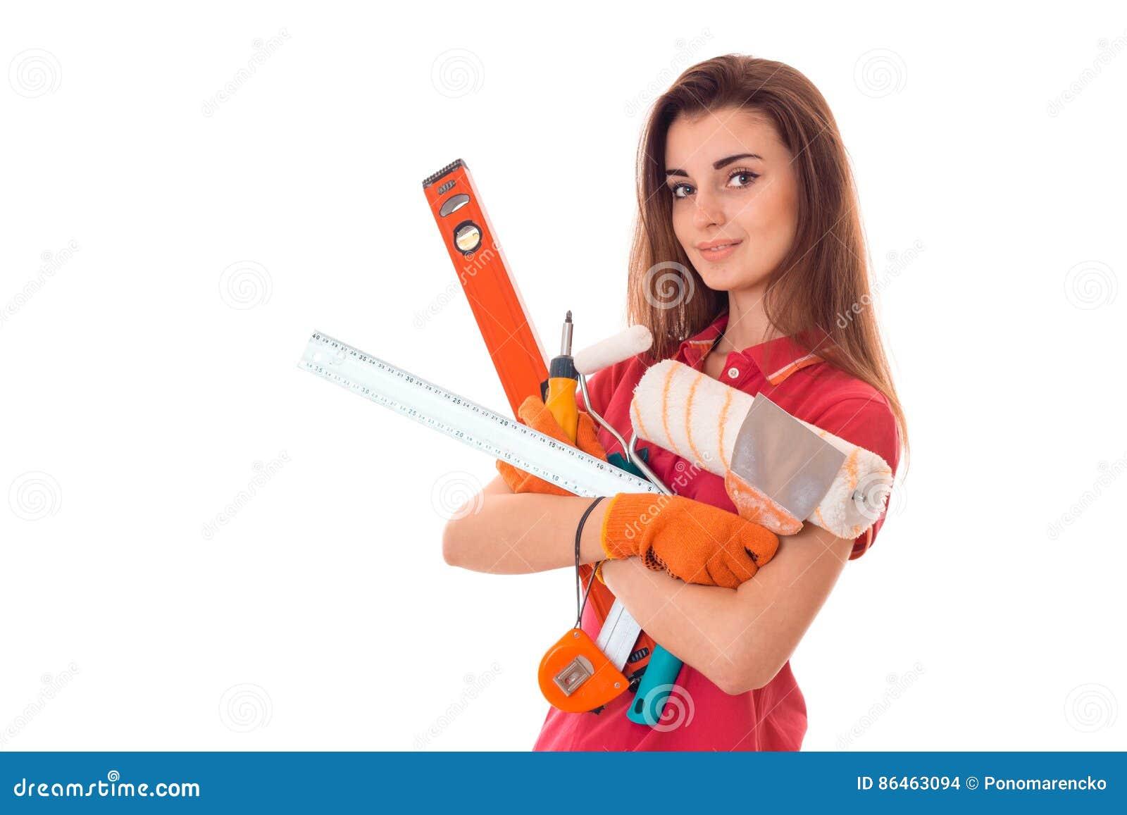 Porträt der jungen attraktiven Brunettegebäudefrau in der roten Uniform mit Werkzeugen in den Händen macht Erneuerung und das Bet