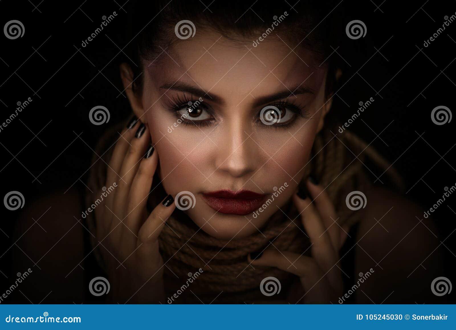 Porträt der jungen Frau über Seil mit schwarzem Hintergrund Mode, außerordentliches Make-up und Face lifting-Konzept