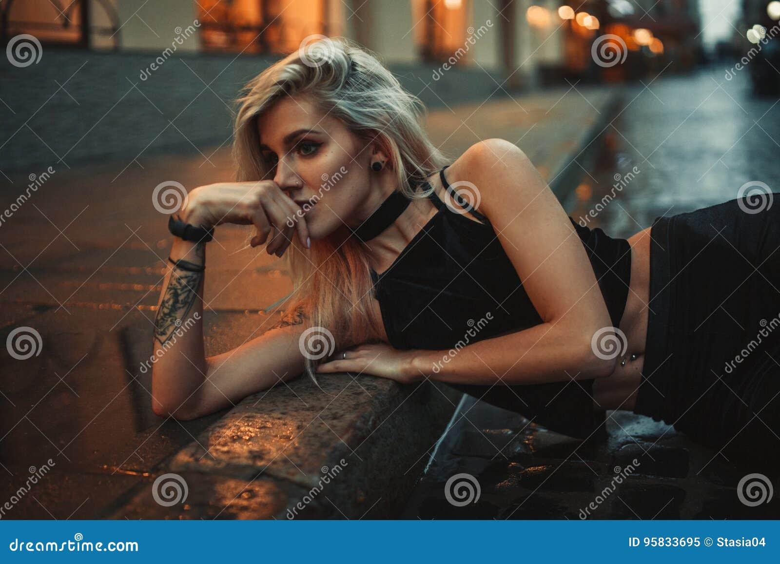 Porträt der jungen Frau, das auf nasser Pflasterung auf Stadtstraße am Vorabend liegt