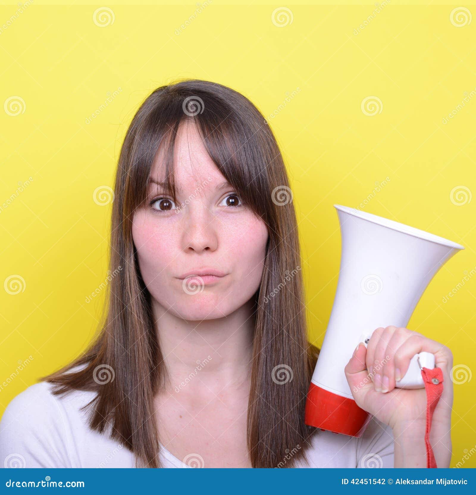 Porträt der jungen Frau schreiend mit einem Megaphon gegen Gelb