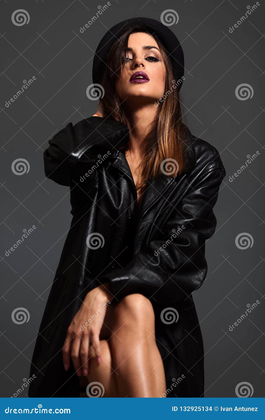 Porträt der jungen Frau in der schwarzen Lederjacke und im Hut