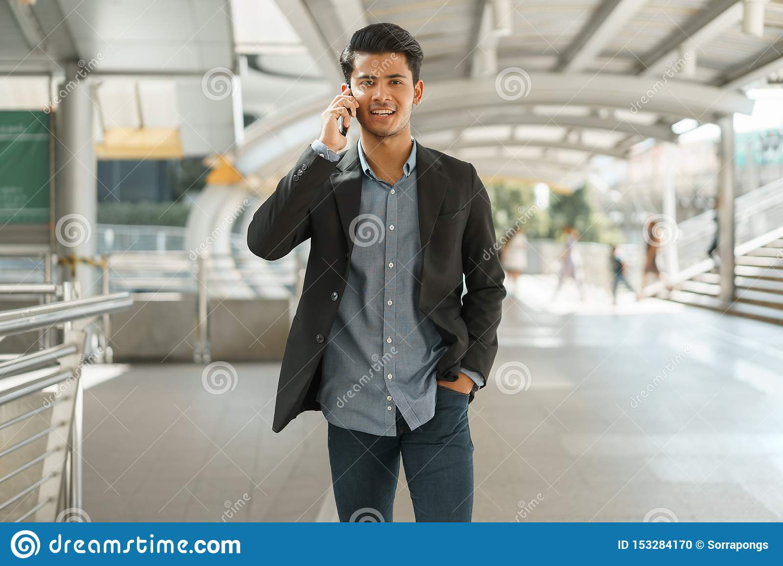 Porträt der jungen Geschäftsmannstellung im äußeren Büro und der Unterhaltung auf Smartphone Asiatischer Geschäftsmann-Abnutzungs