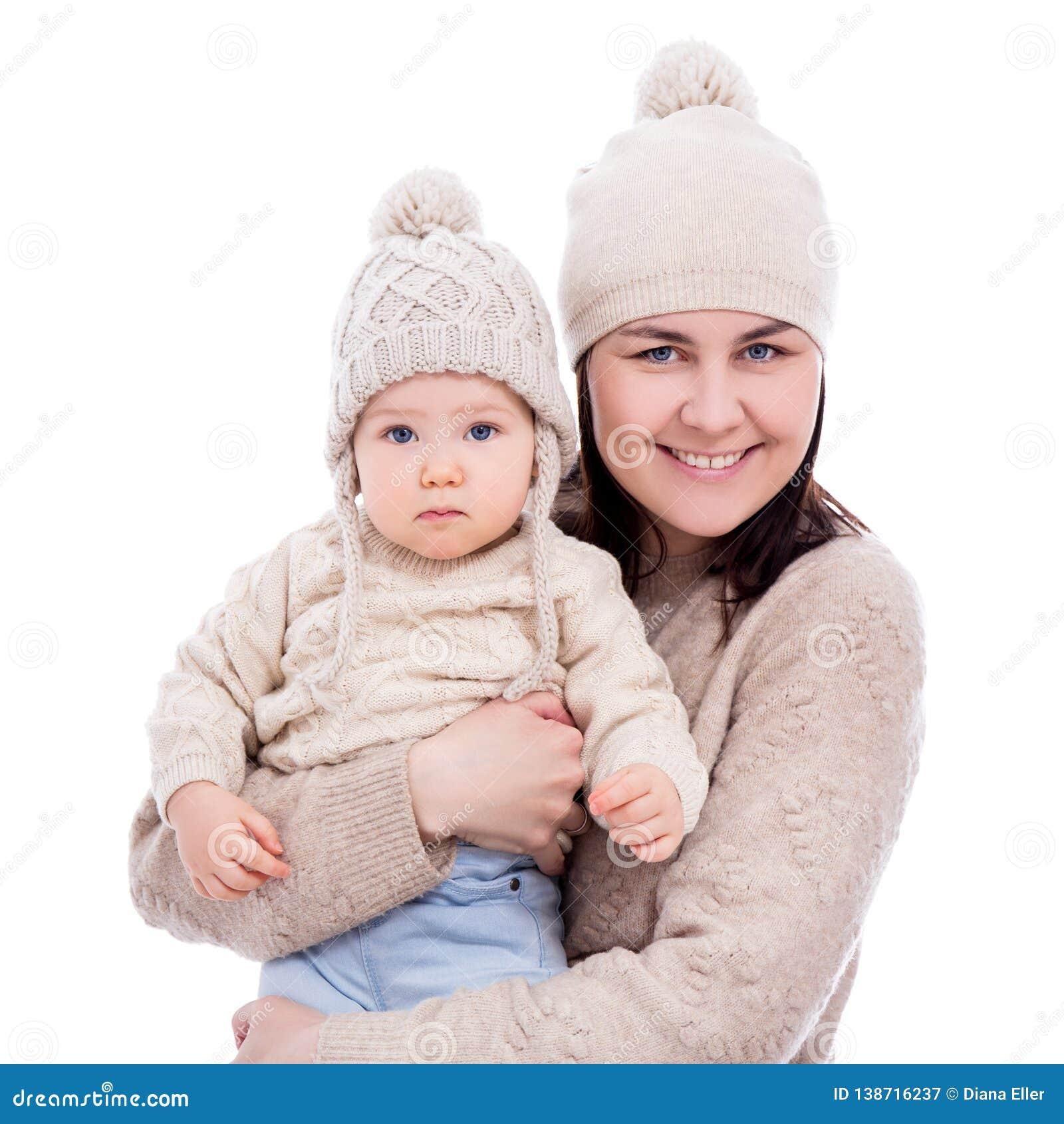 Porträt der jungen Mutter und des netten Babys in der Winterkleidung lokalisiert auf Weiß