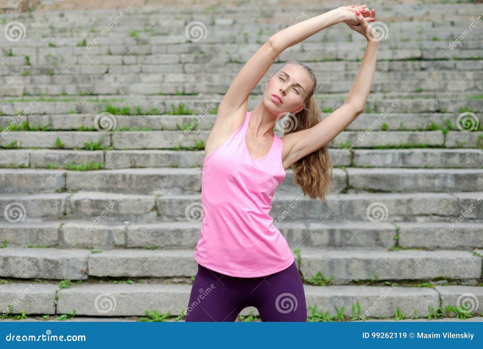 Porträt der jungen sportlichen Frau im Sportkleid tut das Ausdehnen Übungen von den im Freien
