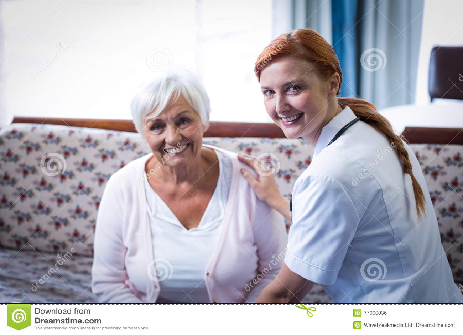 Porträt der lächelnden älteren Frau und der Ärztin im Wohnzimmer