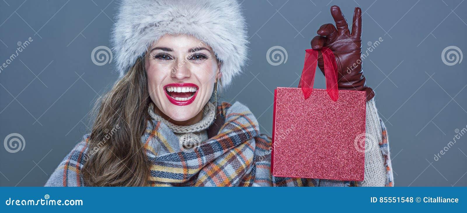 Porträt der lächelnden eleganten Frau, die kleine rote Einkaufstasche zeigt