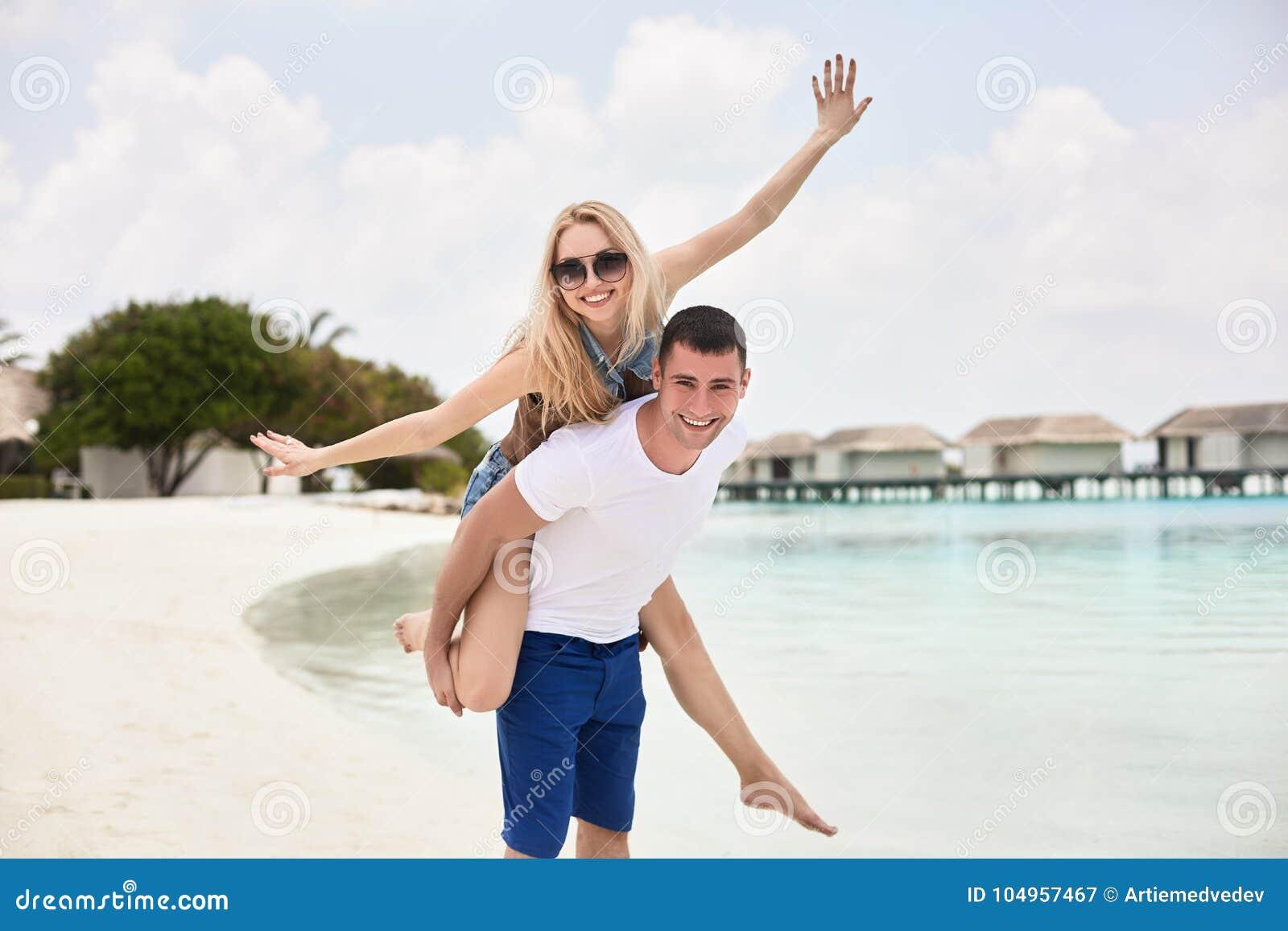 Porträt der lächelnden tragenden Frau des Mannes auf seinem zurück entlang dem Seeufer Kerl, der piggyback der Freundin Fahrt dur