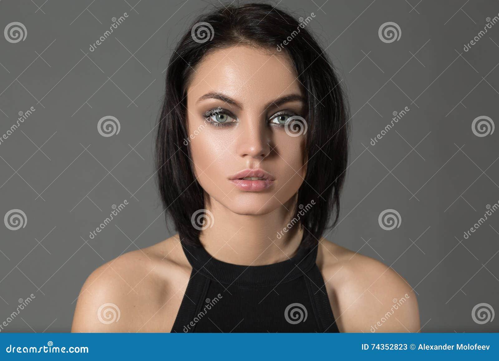 Porträt der modernen netten Frau des kurzen Haares, die Kamera auf Grau betrachtet