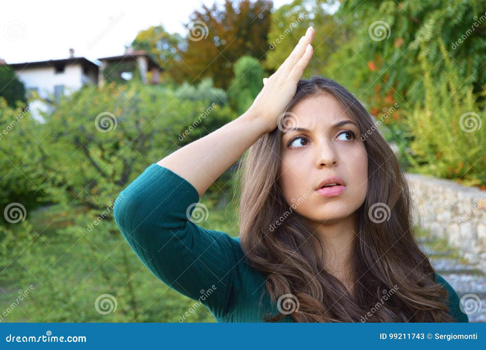 Porträt der reizenden Brunettefrau erinnerte sich an etwas und hält eine Hand