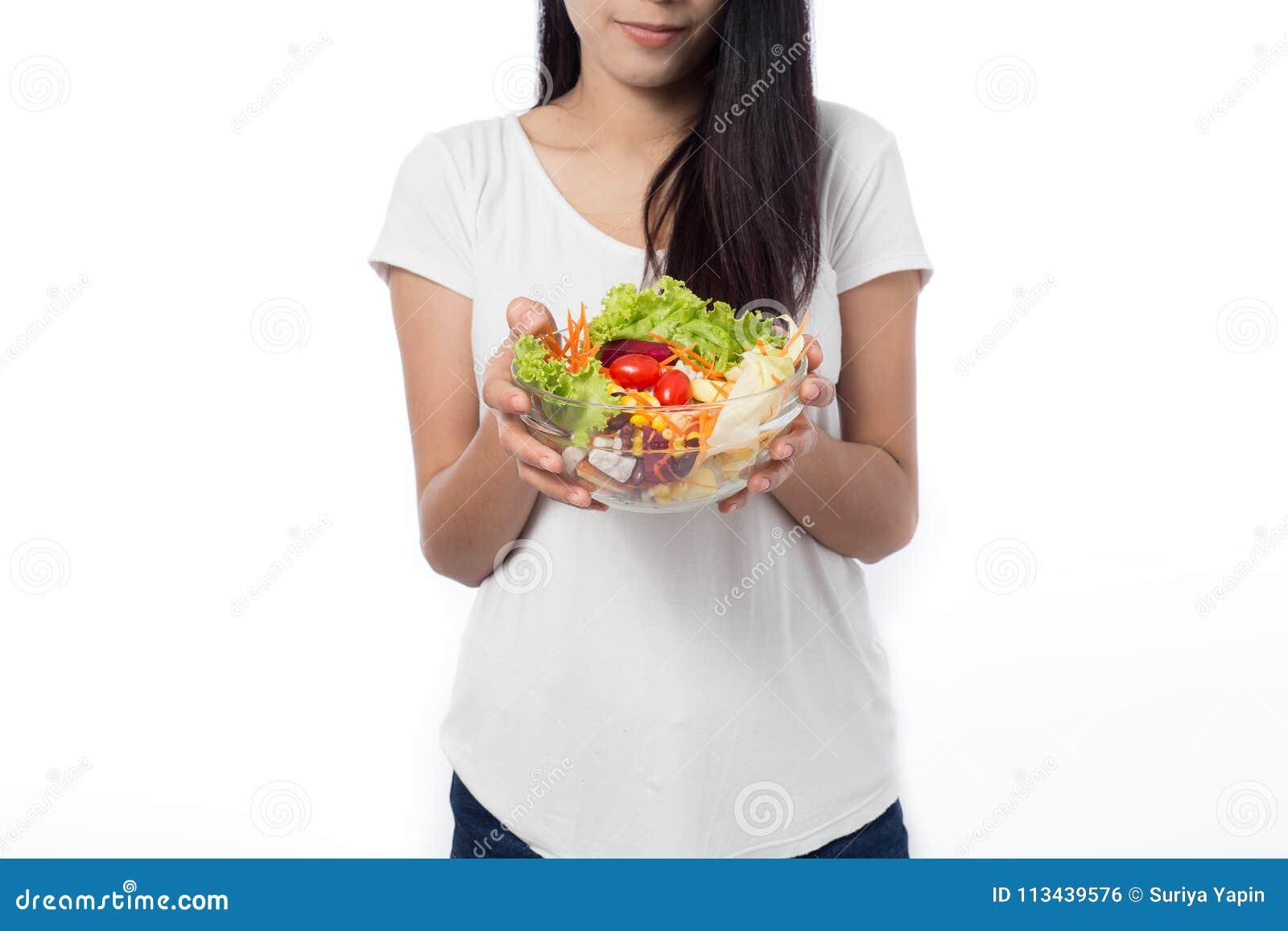 Porträt der schönen asiatischen jungen Frau, die Gemüsesalat isst