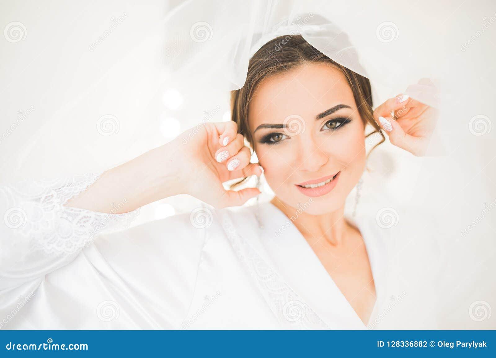 Porträt der schönen Braut mit Modeschleier am Hochzeitsmorgen