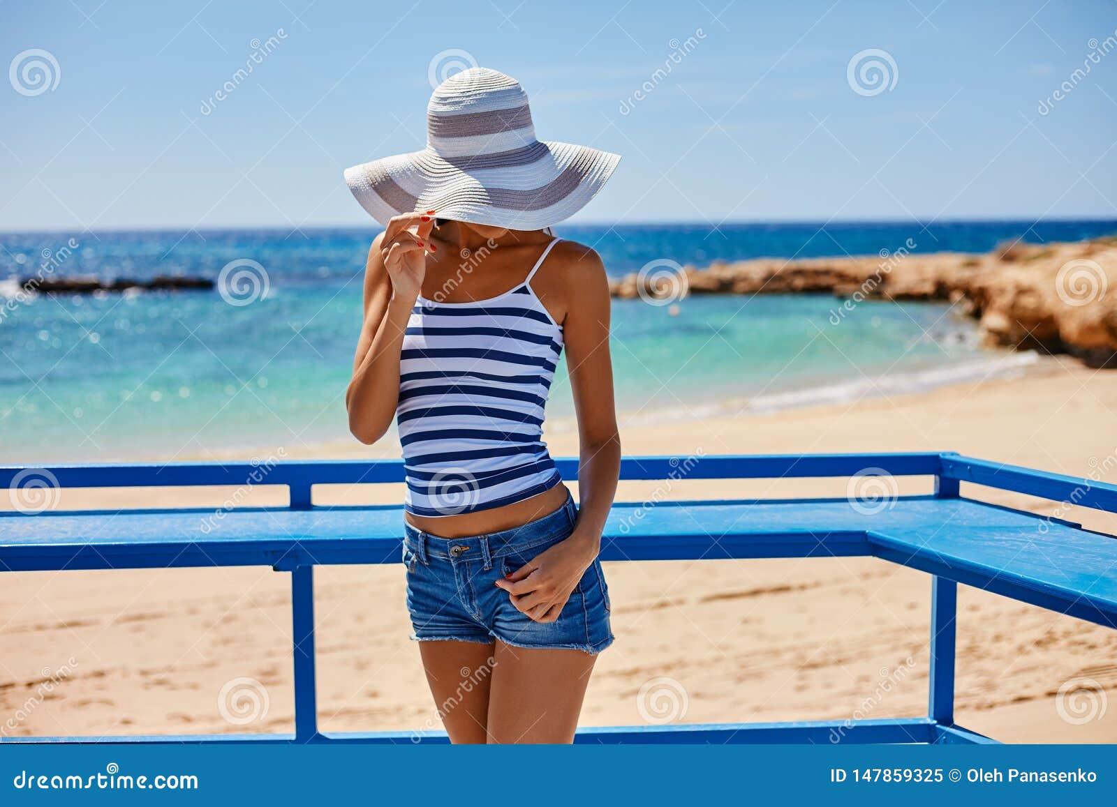 Portr?t der sch?nen gebr?unten Frau an der Seek?ste in der Hut- und Retrostilkleidung Hei?er Sommertag und helles sonniges Licht