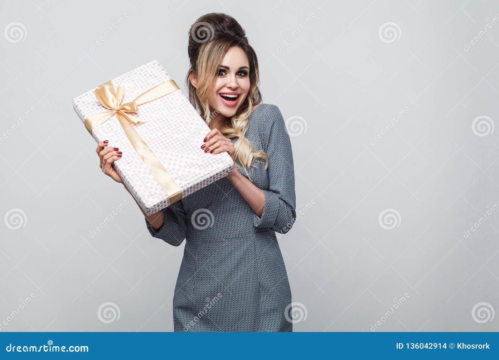 Porträt der schönen jungen Frau des emotionalen Vergnügens in der grauen dem Kleiderstellung und -c$zeigen Sie anwesend mit gelbe