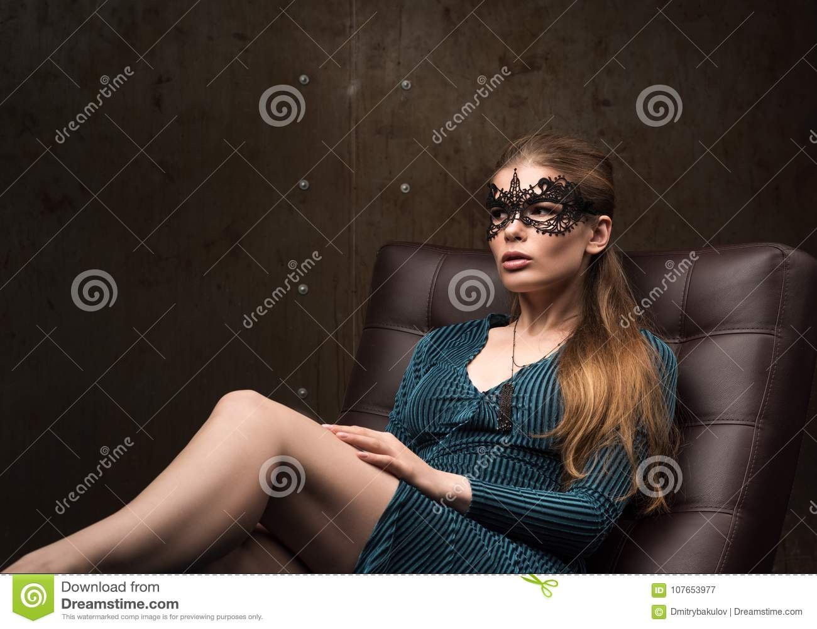Porträt der schönen jungen Frau, die auf der Couch sitzt Schauen Sie vorsichtig