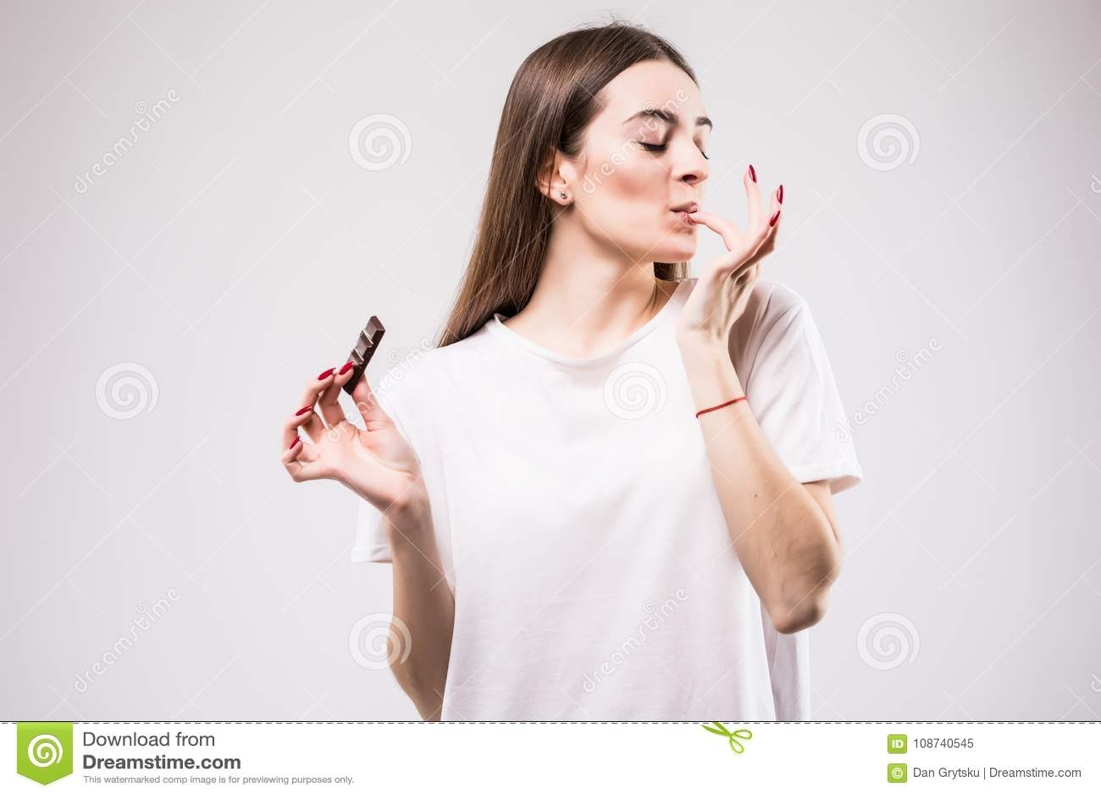 Porträt der schönen lächelnden Frau genießen, die Schokolade zu essen, die auf grauem Hintergrund lokalisiert wird Apfel- und Ban