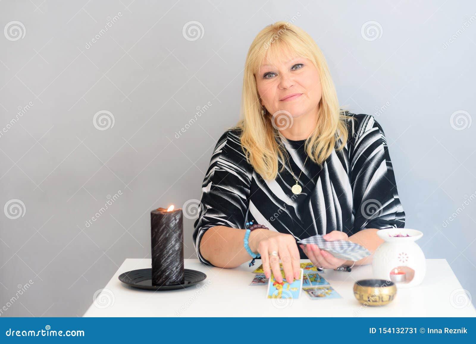 Porträt der schönen Mittelalterfrau sitzt nahe einem Wahrsagerschreibtisch mit Karten und Kerzen eines Tarocks