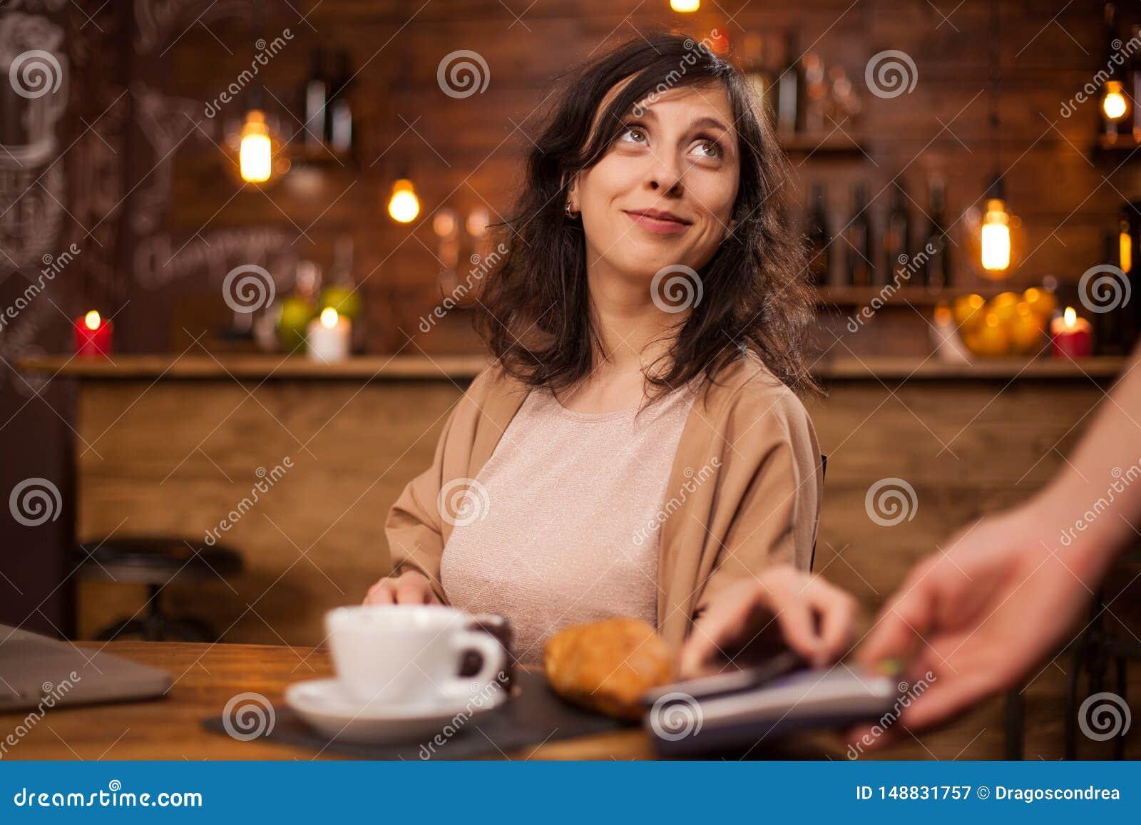Porträt der Schönheit oben betrachtend barista und Kaffee unter Verwendung der modernen Zahlung in einer Kaffeestube zahlend