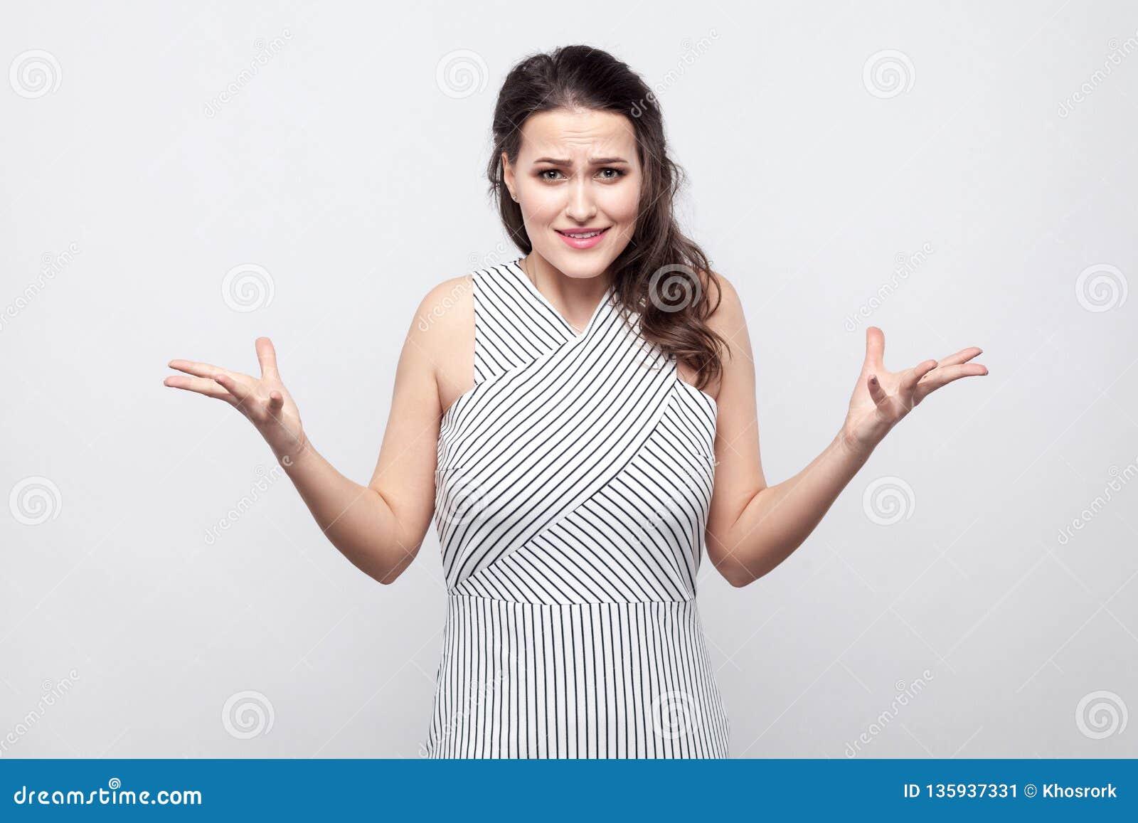 Porträt der verwirrten schönen jungen brunette Frau mit Make-up und gestreifter Kleiderstellung und dem Betrachten der Kamera mit