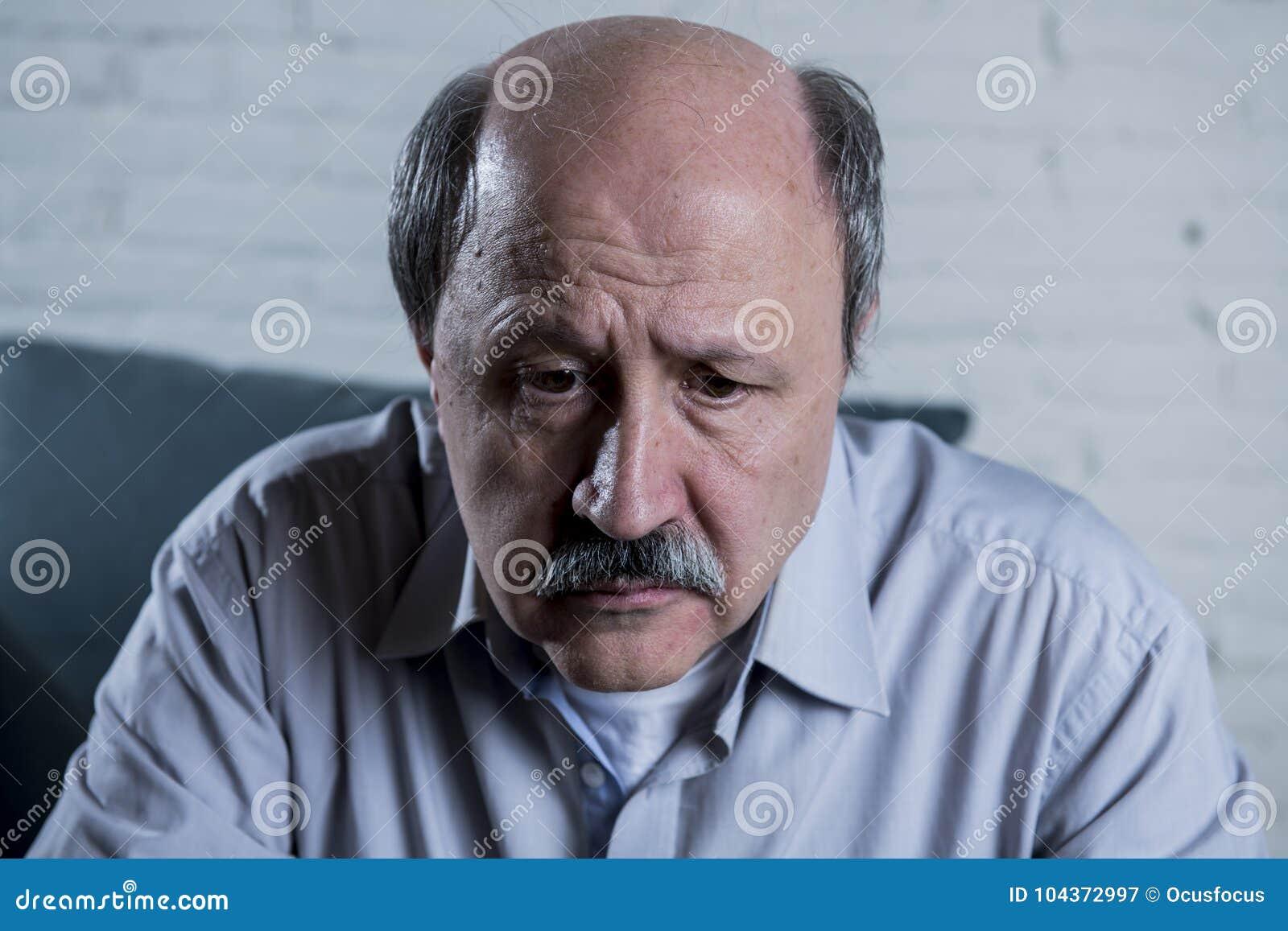 Porträt des älteren reifen alten Mannes auf seinen zu Hause allein traurigen und besorgten leidenden Schmerz des Gefühls der Couc