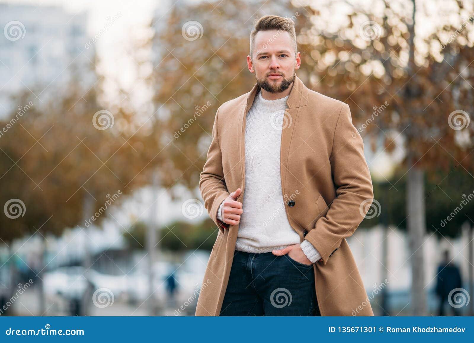 Porträt des überzeugten Mannes im braunen Mantel und in der weißen Strickjacke