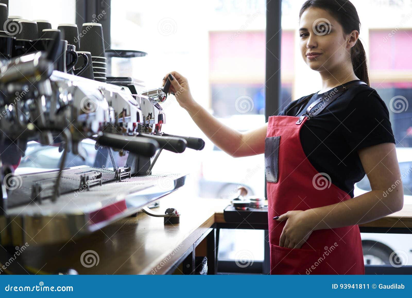 Porträt des attraktiven weiblichen barista, das in der Cafeteria arbeitet