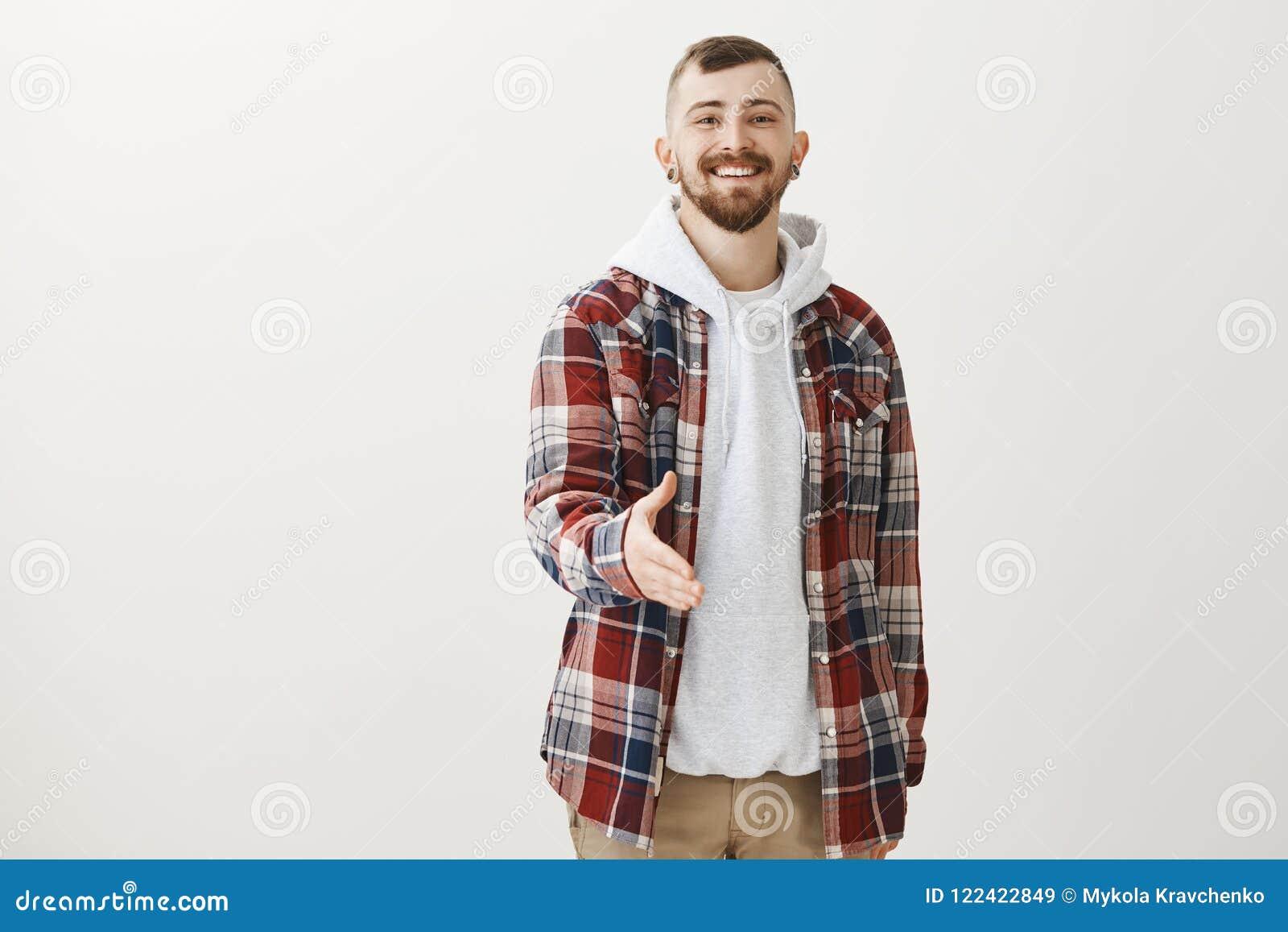 Porträt des confdent freundlich-aussehenden netten Mannes mit Bart und stilvollem Haarschnitt, Hand in Richtung zur Kamera und zu