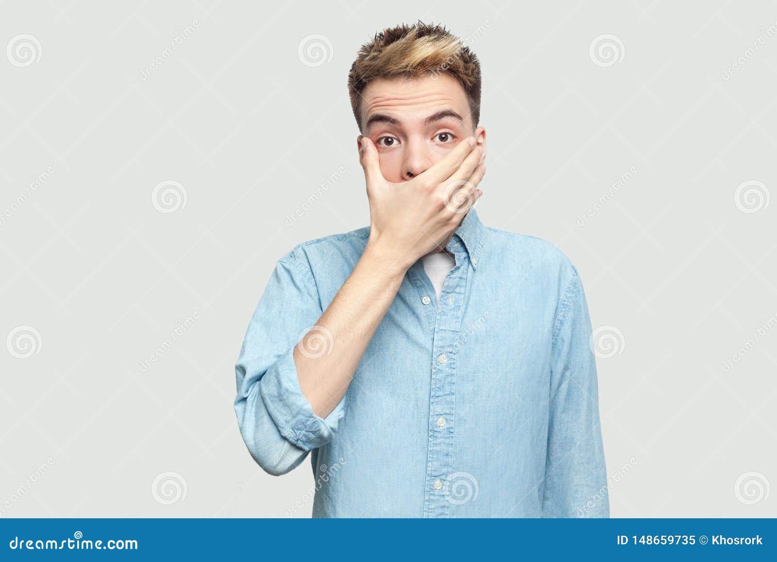 Portr?t des entsetzten h?bschen jungen Mannes in der hellblauen Hemdstellung mit erschrockenem Gesicht, seinen Mund bedeckend und