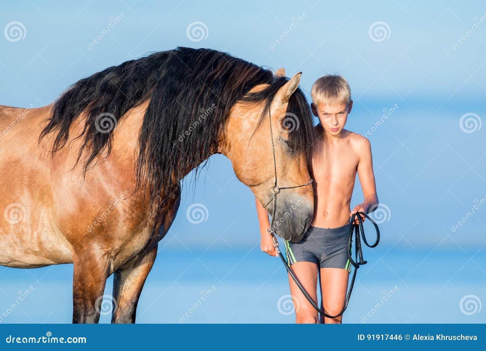 Porträt des ernsten jungen Reiters mit Pferd im Sonnenuntergang