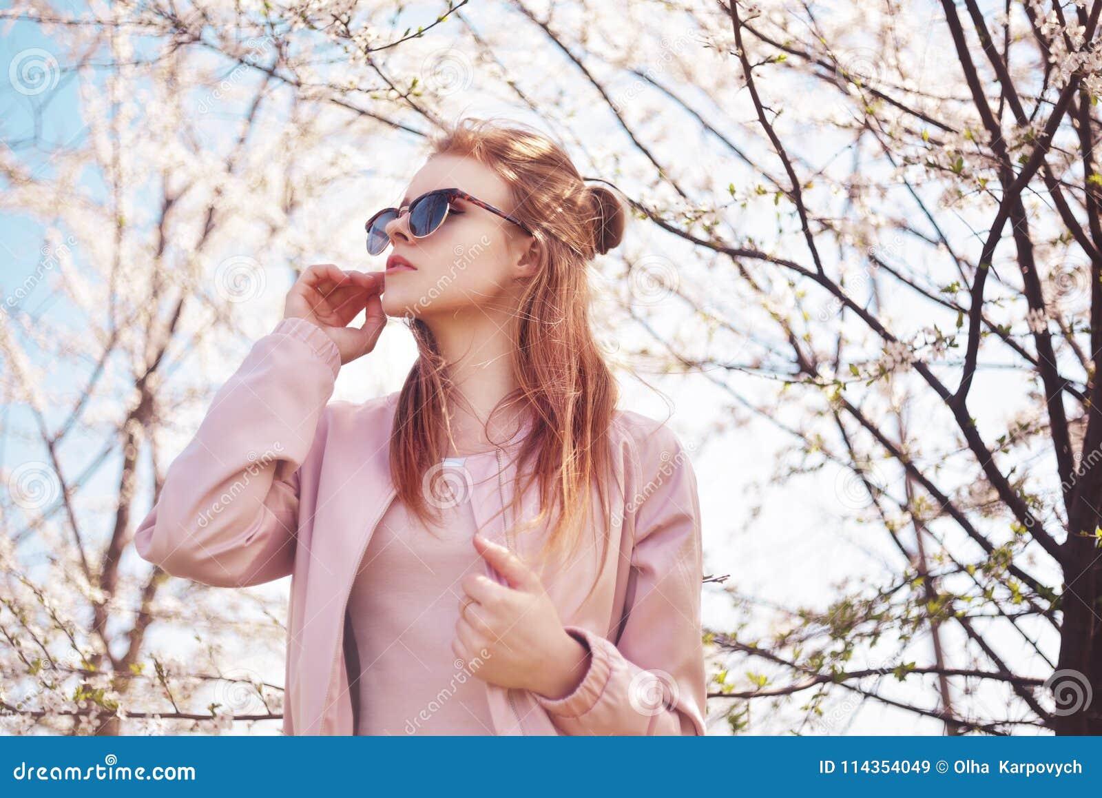 Porträt des Frühlingsmode-Mädchens draußen in blühenden Bäumen Romantische Frau der Schönheit in den Blumen in der Sonnenbrille S