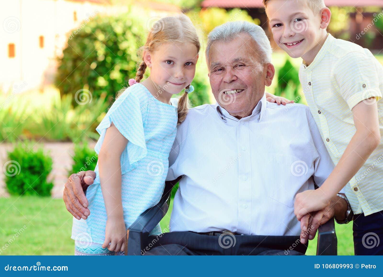 Porträt des glücklichen alten Großvaters und der netten Kinder
