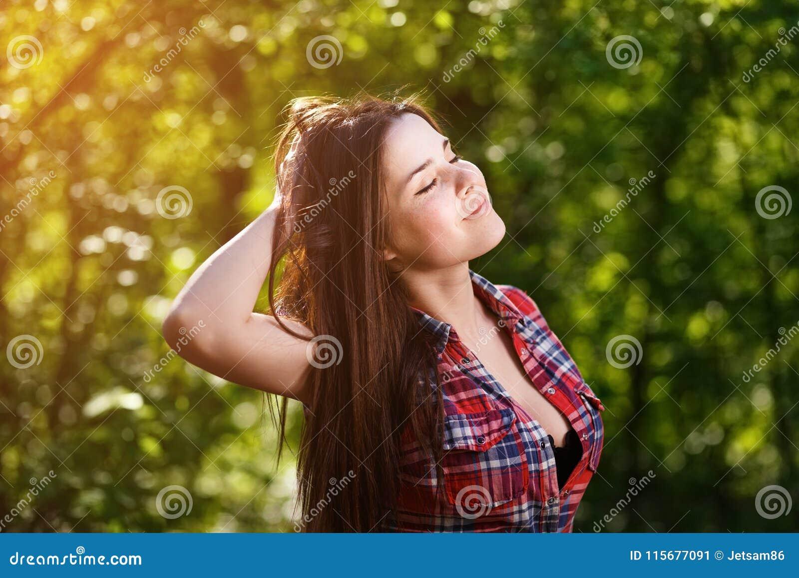 Porträt des glücklichen jungen lächelnden Mädchens, welches das Leben auf Hintergrund genießt