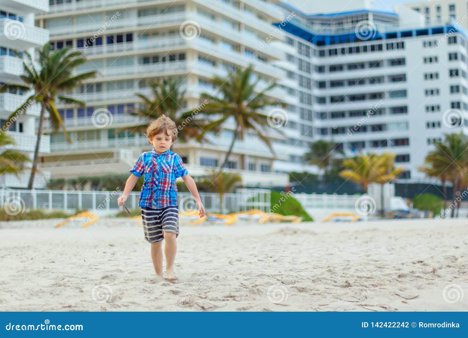 Porträt des glücklichen Kleinkindjungen auf dem Strand von Ozean Lustiges nettes Kind, das Ferien macht und Sommer genießt Gesund