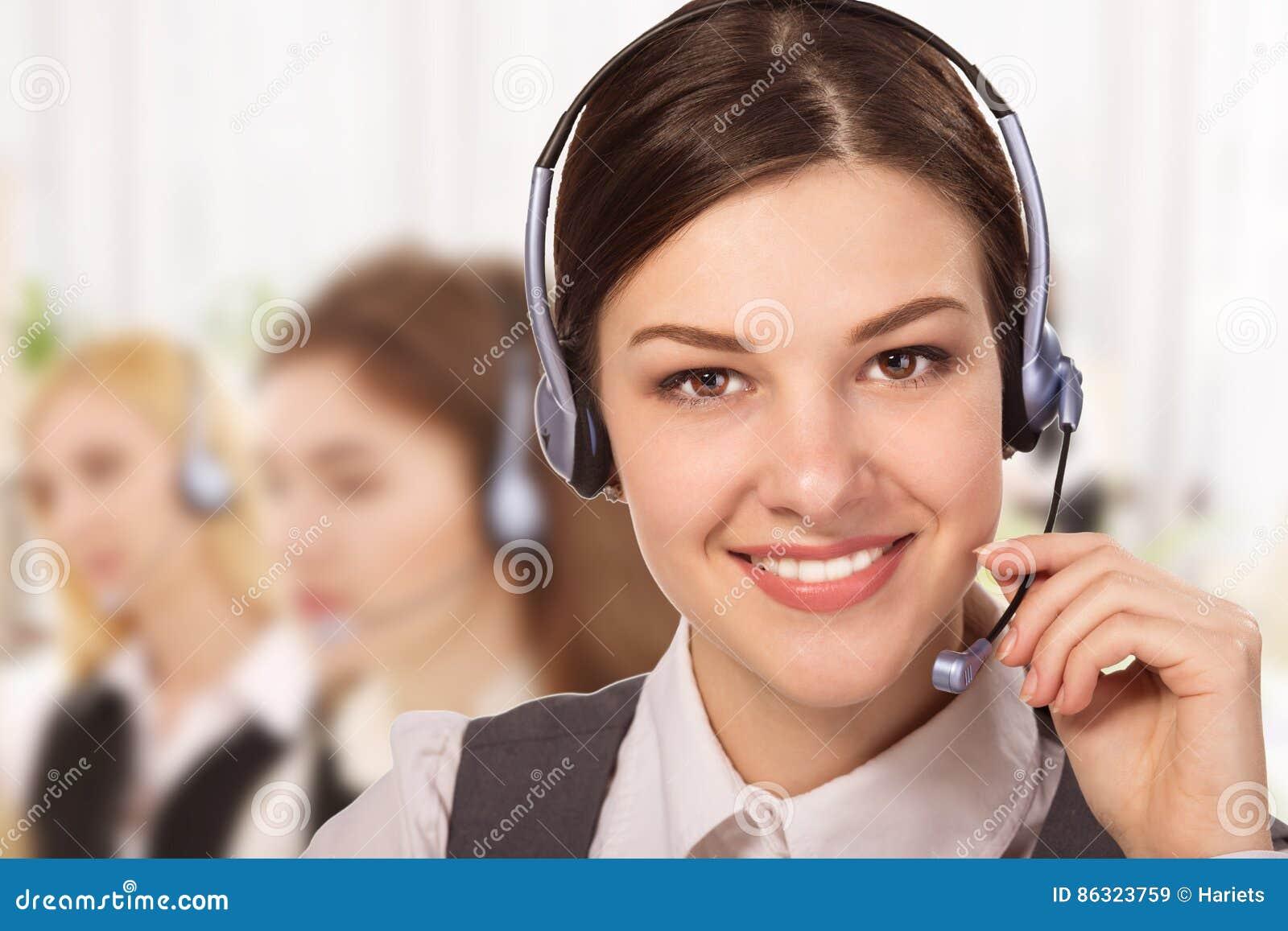 Porträt des glücklichen lächelnden netten Stütztelefonbetreibers im Kopfhörer