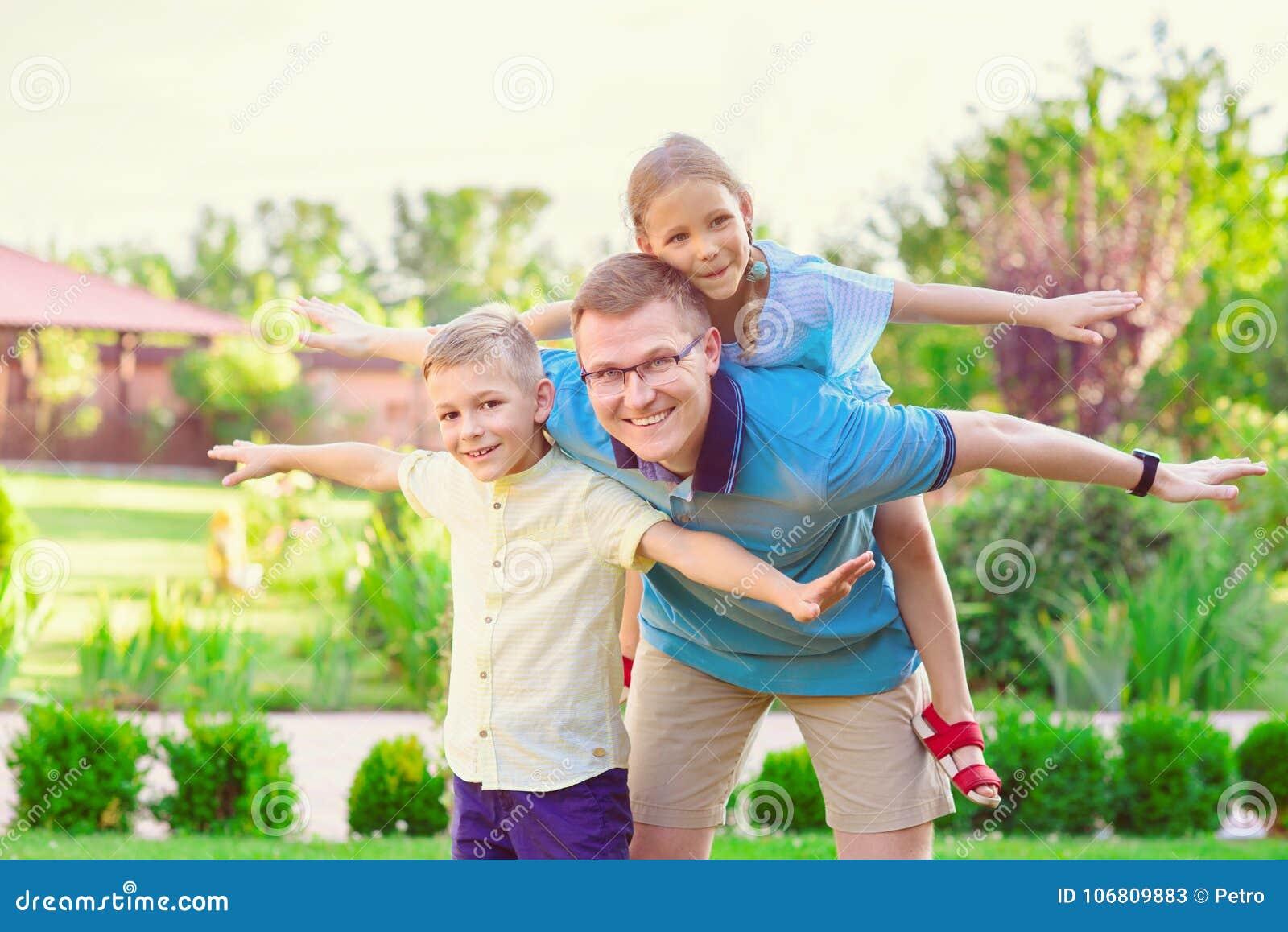 Porträt des glücklichen Vaters und zwei netten der Kinder, die an courty spielen