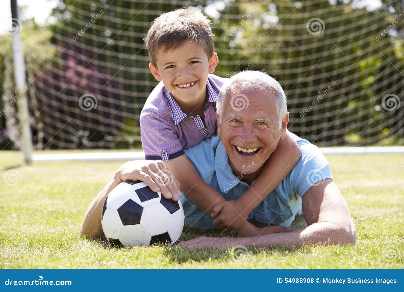 Porträt des Großvaters und des Enkels mit Fußball