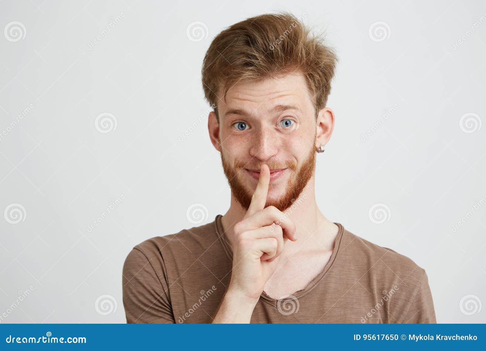 Porträt des jungen gutaussehenden Mannes mit dem Bart, der das lächelnde Darstellen der Kamera, zum von Ruhe über weißem Hintergr