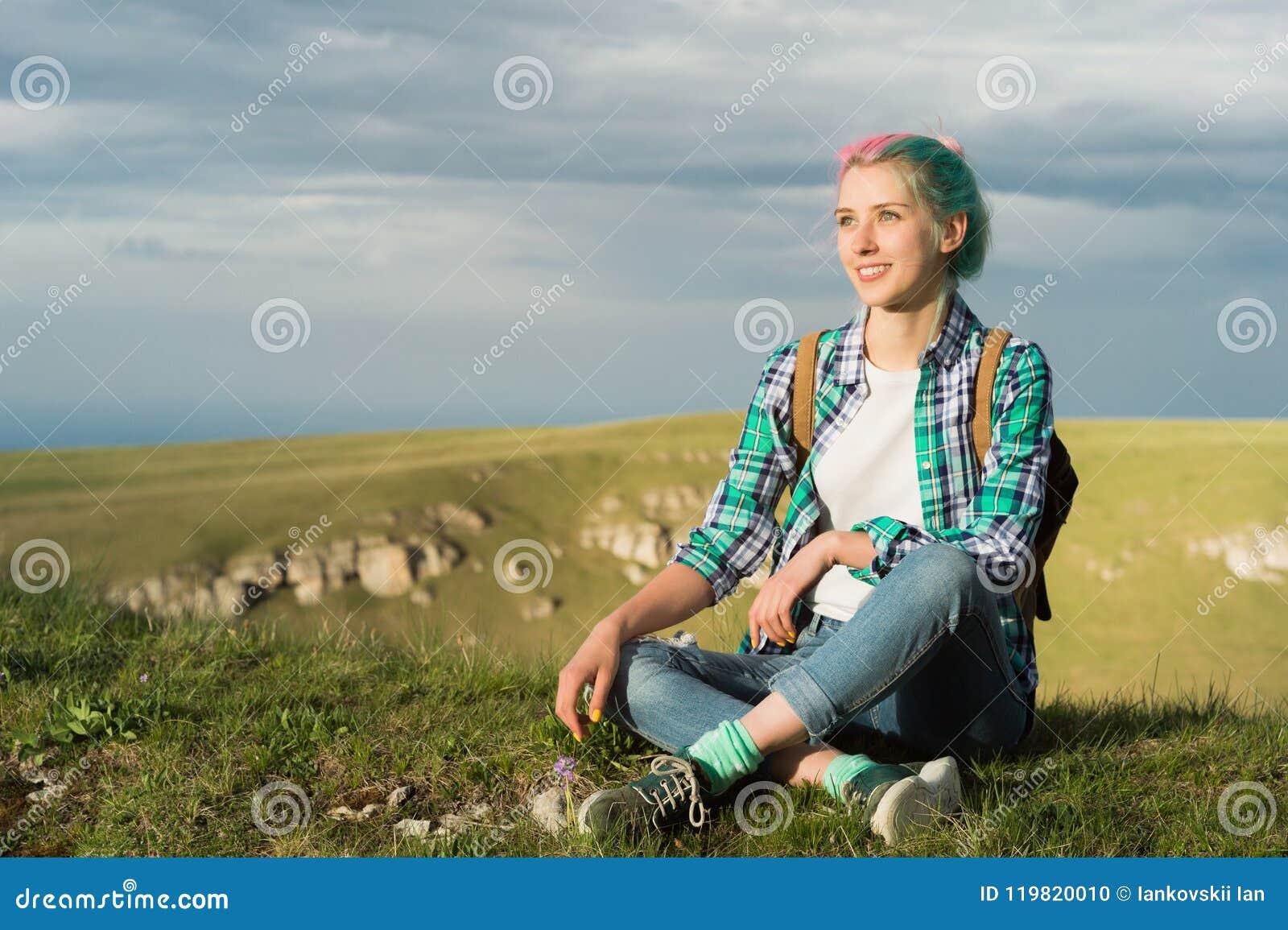 Porträt des jungen lächelnden Frauenreisenden mit dem mehrfarbigen Haar In den Bergen am Abend mit a hoch sitzen