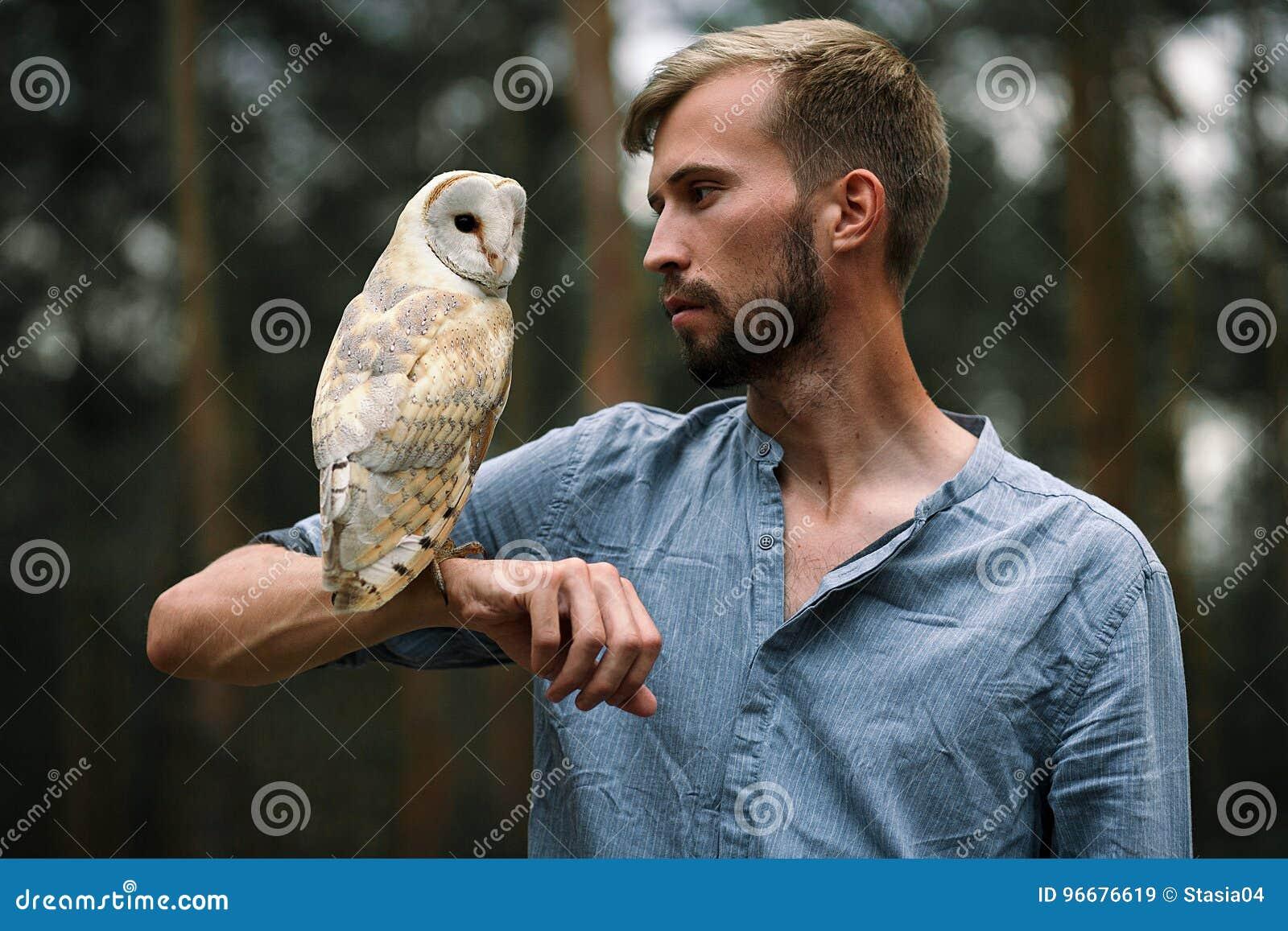 Porträt des jungen Mannes im Wald mit Eule in der Hand Nahaufnahme