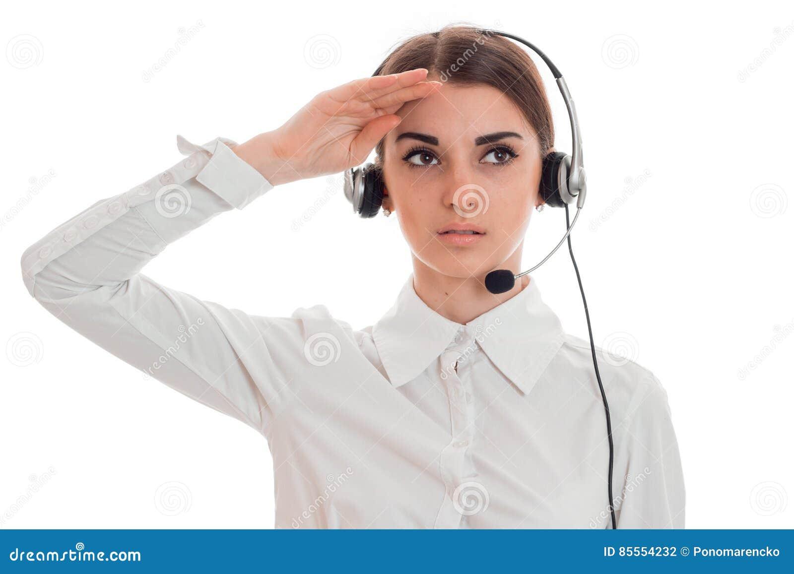 Porträt des jungen schönen Fernsprechamtmädchens im weißen Hemd mit den Kopfhörern lokalisiert auf Hintergrund im Studio