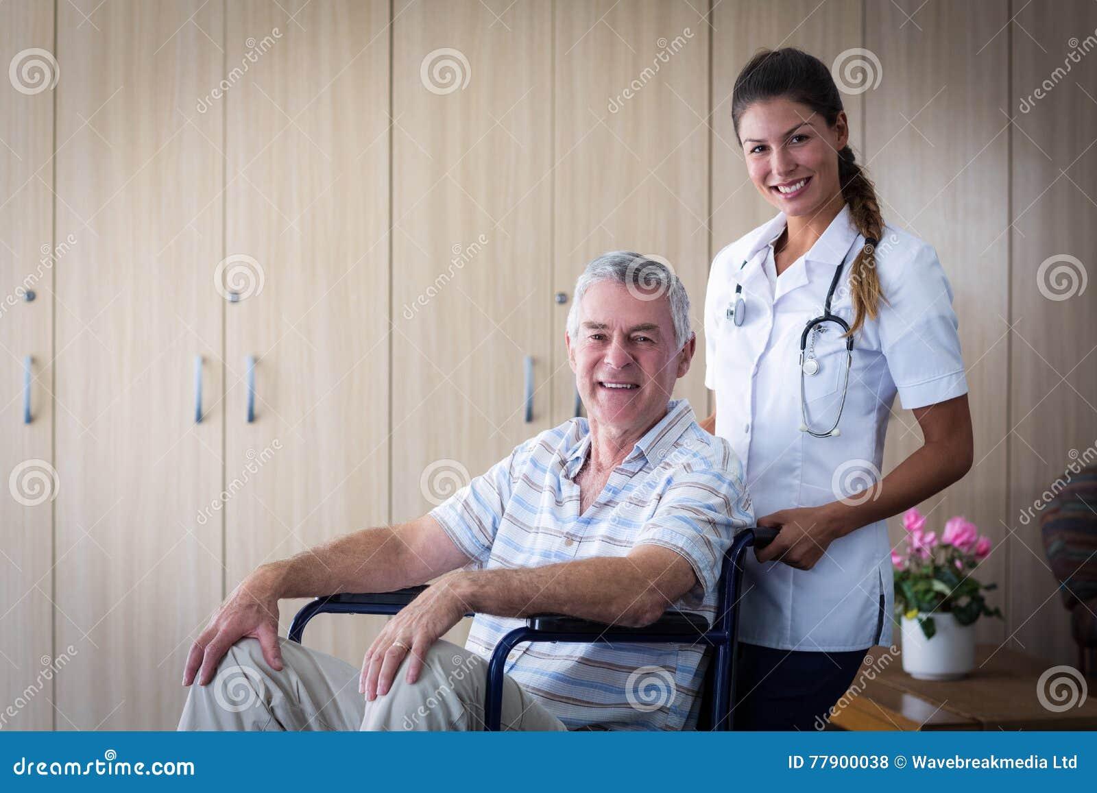 Porträt des lächelnden älteren Mannes und der Ärztin im Wohnzimmer