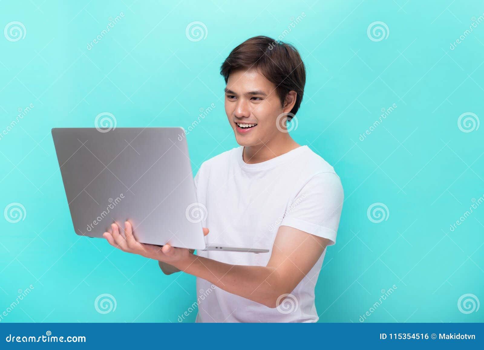 Porträt des lächelnden jungen Mannes mit dem Laptop lokalisiert auf Blau