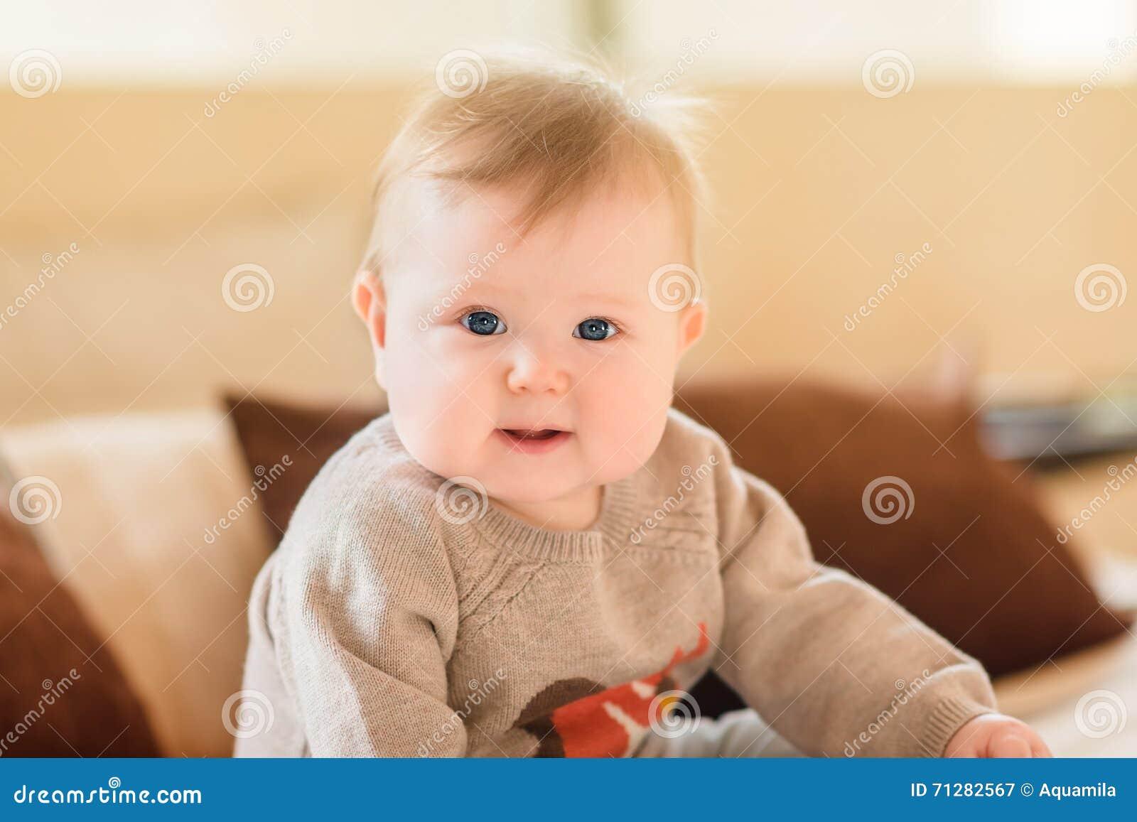Porträt des lächelnden kleinen Kindes mit dem blonden Haar und blauen den Augen, welche die gestrickte Strickjacke sitzt auf Sofa