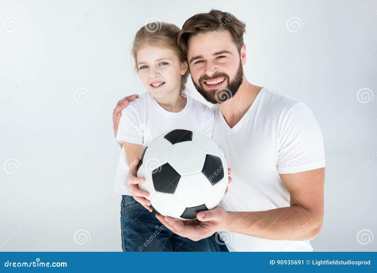 Porträt des lächelnden Vaters und der Tochter, die Fußball halten